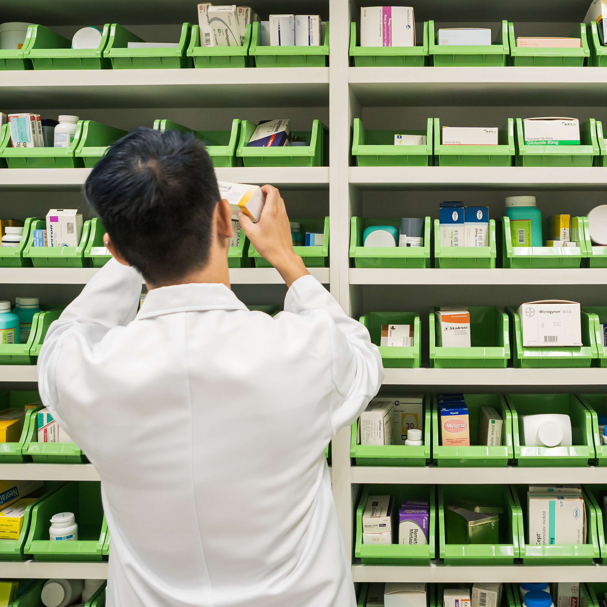A pharmacy student in front of a dispensing cabinet.